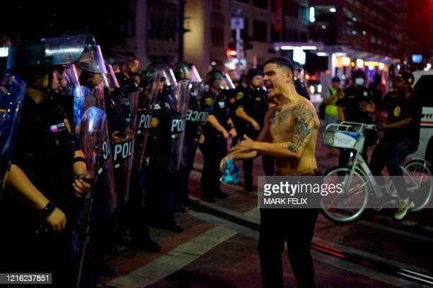 A protester confronts a row of police officers during a Justice 4 George Floyd demonstration over the death of George Floyd a black man who died...