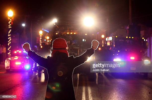 A protester confronts police vehicles with her hands up as police attempt to clear the streets as on November 25 2014 in Ferguson Missouri Over 2000...