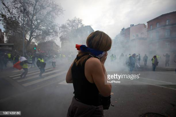 A protester covers her mouth after riot police launched tear gas Protesters called 'Gilets jaunes' protest for the third time in three weeks Protest...