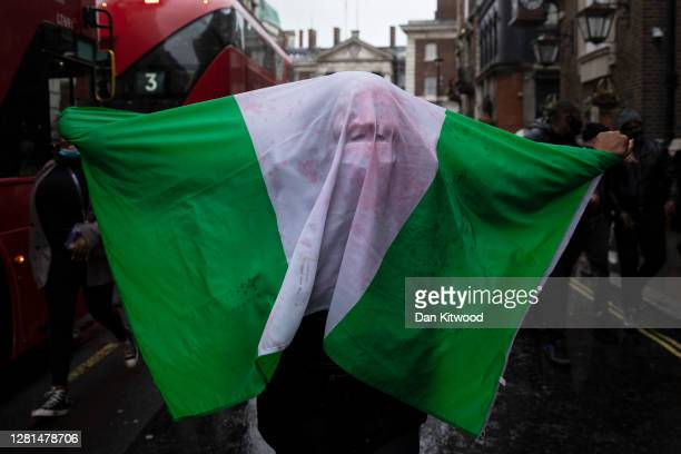 Protester covers themselves in a Nigeria flag outside the Nigerian High Commission during a protest calling for the end of police killings of the...