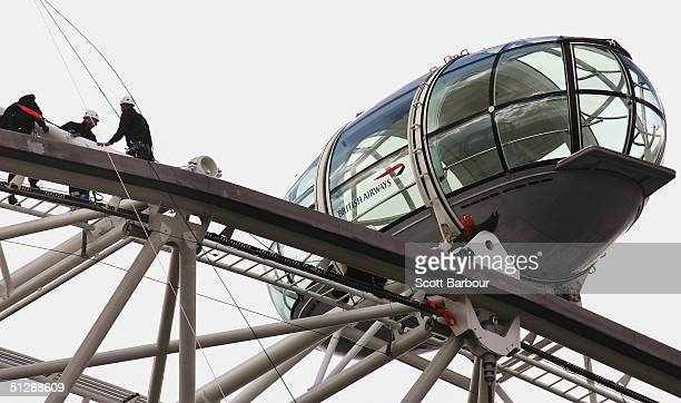 Protester David Chick is approached by police climbers as he sits atop of the London Eye dressed in a Spiderman suit on September 11, 2004 in London,...