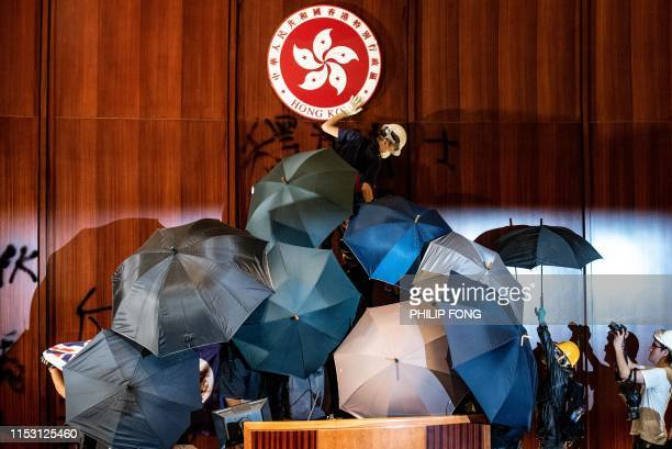 TOPSHOT A protester defaces the Hong Kong emblem after protesters broke into the government headquarters in Hong Kong on July 1 on the 22nd...