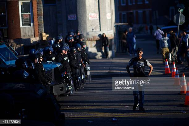 A protester defies the required distance between demonstrators and riot police the afternoon after citywide riots over the death of Freddie Gray on...