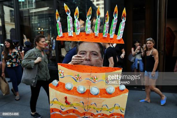 A protester displays a cakeshape placard with a picture of former Federal Bureau of Investigation director James Comey during a demonstration against...