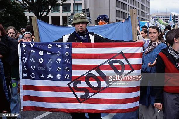 A protester displays a modified American flag with the stars replaced by the logos of international American corporations such as Apple Computer IBM...