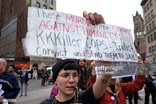A protester displays a placard at the Union Square in New York on April 14 2015 during a demonstration against the recent shooting death of Walter...