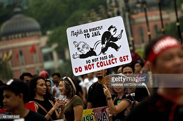 A protester displays a placard during a May Day rally at Independence square in Kuala Lumpur on May 1 2014 Thousands gathered in Malaysia's capital...