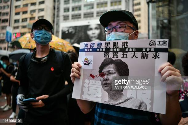 Protester displays a poster bearing an image of Hong Kong Chief Executive Carrie Lam in the popular shopping district of Causeway Bay in Hong Kong on...