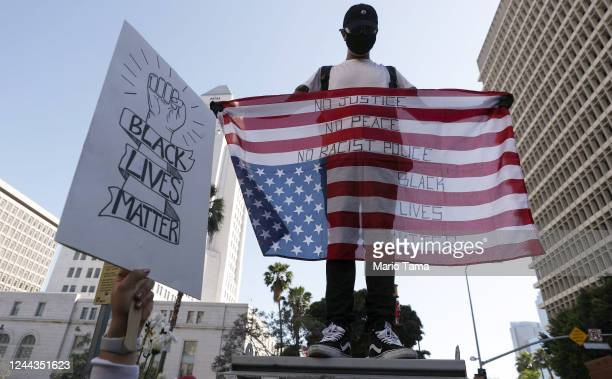 A protester displays an upside down US flag outside the District Attorney's office during a peaceful demonstration over George Floyd's death on June...