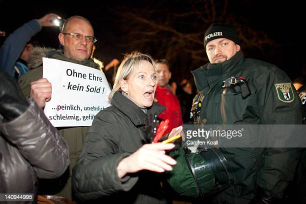 A protester disputes with the police outside Bellevue Palace during the Zapfenstreich or taps farewell ceremony taking place in the Bellevue garden...