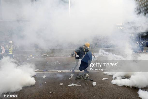 A protester douses a tear gas canisters with water outside the Legislative Council during a protest against a proposed extradition law in Hong Kong...