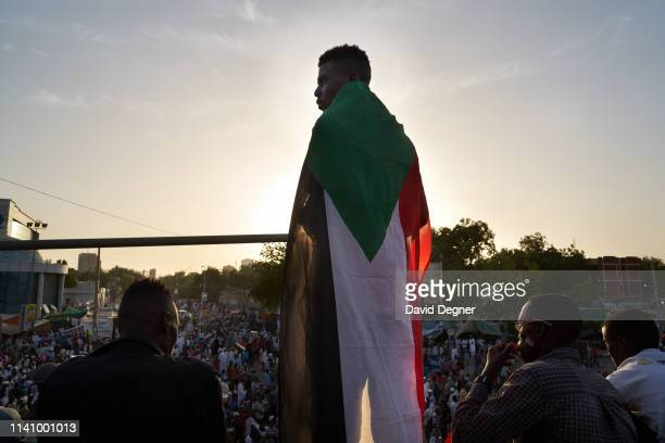 Protester draped in the Sudanese flag stands above the sit-in on May 03, 2019 in Khartoum, Sudan. Thousands of demonstrators continued their mass...