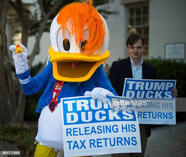 A protester dress like Donald Duck hands out 'Trump Ducks' while protesting Republican presidential nominee Donald Trump's lack of tax returns...