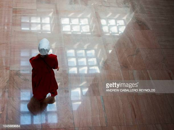 A protester dressed as a character from the novelturnedTV series The Handmaid's Tale walks into the Senate Hart building during a rally against...