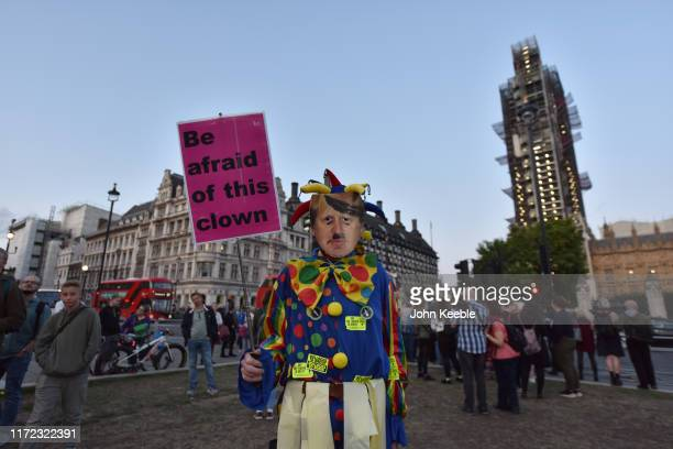 A protester dressed as a clown and wearing a Boris Johnson mask stands on Parliament Green outside the Houses of Parliament on September 04 2019 in...