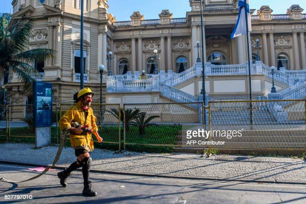 TOPSHOT A protester dressed as a firefighter and using a clown's red nose participates in a protest about delayed payment of salaries of public...