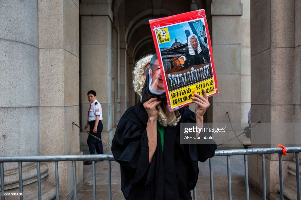 A protester dressed as a judge and with a mask of Chinese President Xi Jinping stands outside the Court of Final appeal after marching in Hong Kong on August 20, 2017, to protest the jailing of Joshua Wong, Nathan Law and Alex Chow (not pictured), the leaders of Hong Kong's 'Umbrella Movement', after their sentencing at the High Court on August 17. Wong, Law and Chow were handed sentences of six to eight months by the Court of Appeal for their role in 2014's massive Umbrella Movement protests, which called for fully free leadership elections and were an unprecedented challenge to Beijing. /