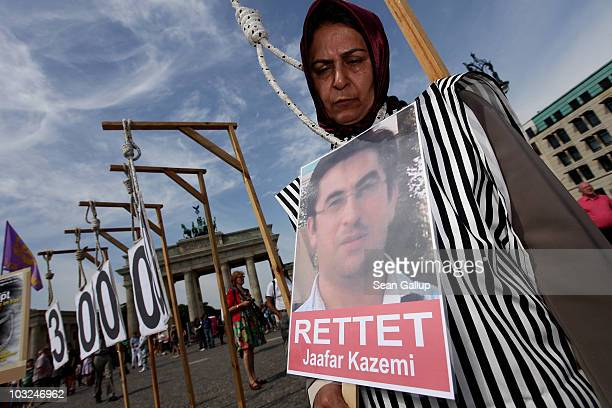 A protester dressed as an execution victim holds a sign that reads Save Jafar Kazemi at a protest by Iranian exiles against Kazemi's execution in...