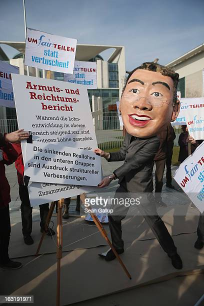 A protester dressed as German Economy Minister Philipp Roesler holds up an altered passage from the government's 4th Poverty And Wealth Report...
