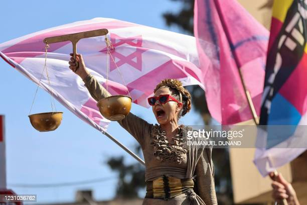 Protester dressed as Lady Justice chants slogans before a pink Israeli flag as she takes part in a demonstration outside the Jerusalem district court...