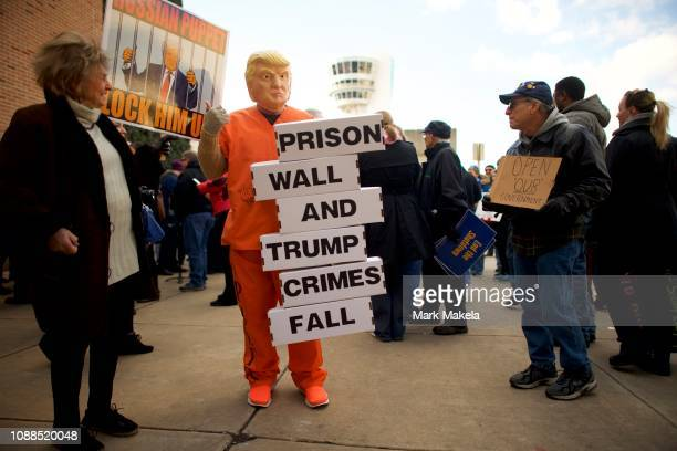 A protester dressed as President Donald Trump holds a placard stating PRISON WALL AND TRUMP CRIMES FALL while demonstrating with Philadelphia Airport...