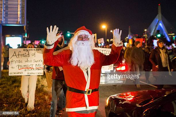 A protester dressed as Santa Claus holds up his hands while marching during a protest against the decision by a Staten Island grand jury not to...