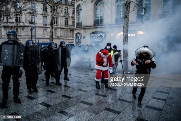 A protester dressed as Santa Claus stands next to French riot police during a demonstration of yellow vests against rising costs of living they blame...