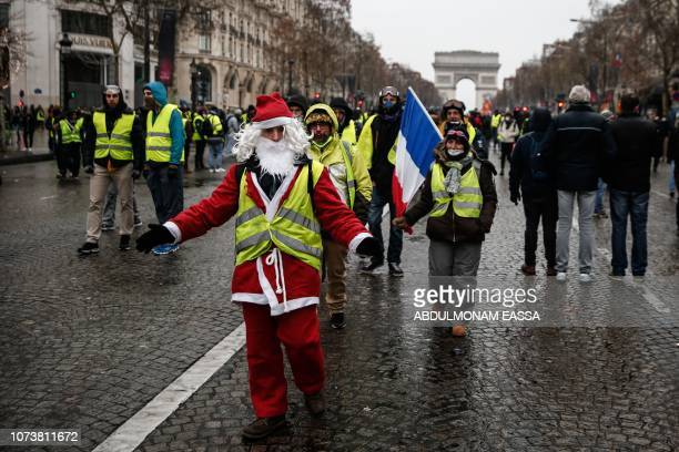 A protester dressed as Santa Claus wears a yellow vest during a demonstration against rising costs of living they blame on high taxes on the...