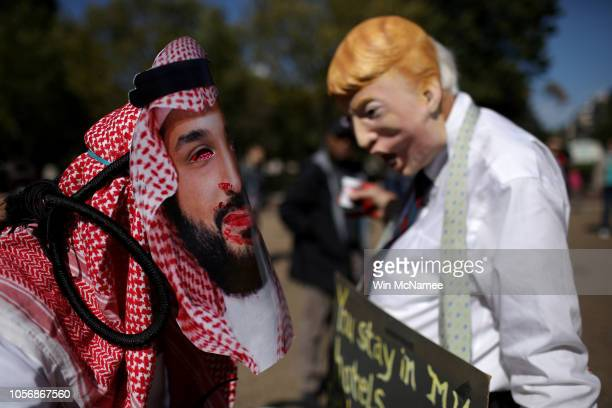 A protester dressed as Saudi Arabian crown prince Mohammad bin Salman and another dressed as US President Donald Trump demonstrate with members of...
