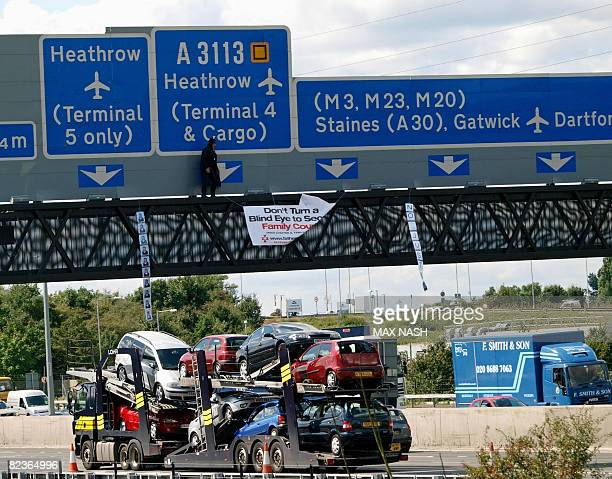Protester dressed as superhero 'Batman' and thought to be a member of Fathers 4 Justice is pictured on a gantry above the M25 motorway near London's...