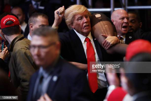 A protester dressed as US President Donald Trump is escorted away by security after he interrupted Vice President Mike Pence's remarks during the...