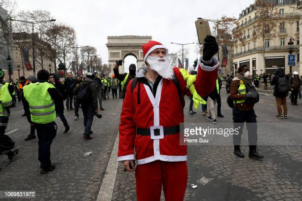 A protester dressed in a santa claus costume takes a selfie on the ChampsÉlysées during the yellow vests demonstration on December 8 2018 in Paris...