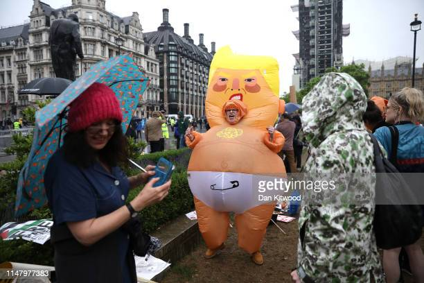 A protester dressed in an inflatable Donald Trump baby costume stands in the rain at Parliament Square as US President Donald Trump and First Lady...