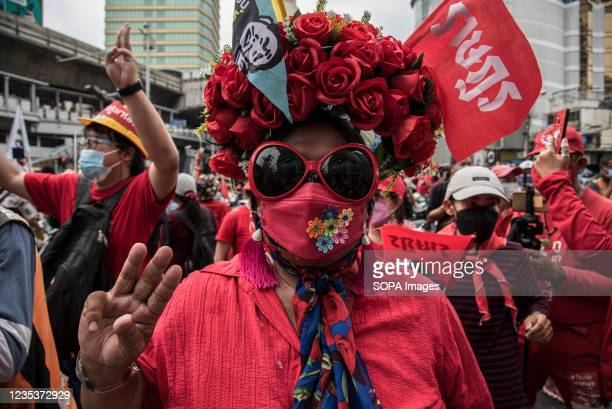 Protester dressed in red with hat of roses makes a three-finger salute during the car mob rally. Anti-government protesters gathered at Asok...