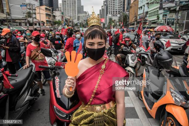 Protester dressed in traditional clothes holds a plastic hand clapper during the car mob rally. Anti-government protesters gathered at Asok...