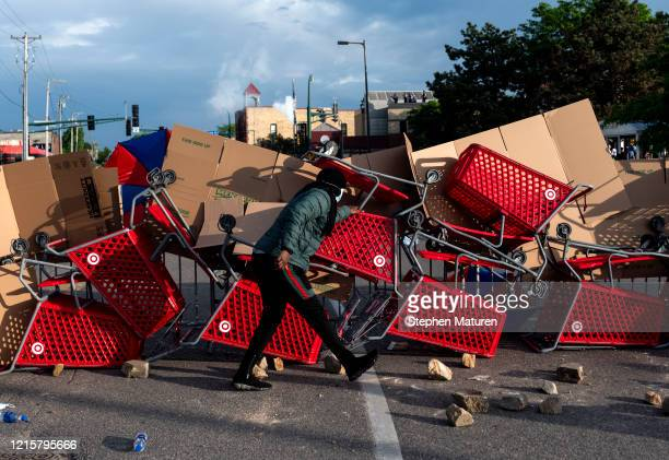 A protester ducks behind a makeshift barricade outside the 3rd Police Precinct on May 27 2020 in Minneapolis Minnesota Four Minneapolis police...