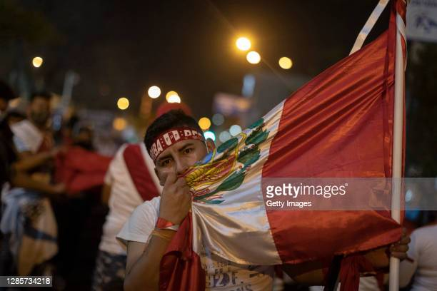 Protester embraces Peru's national flag during a protest against newly appointed interim president Manuel Merino on November 14, 2020 in Lima, Peru....