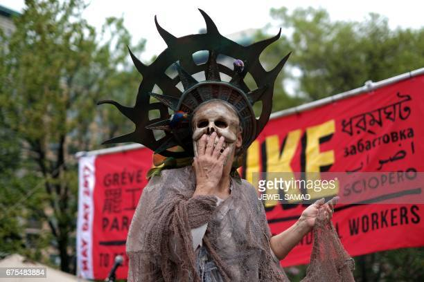 A protester enacts wearing skeleton costume of the Statue of Liberty during a demonstration to mark May Day in New York on May 1 2017 PHOTO / Jewel...