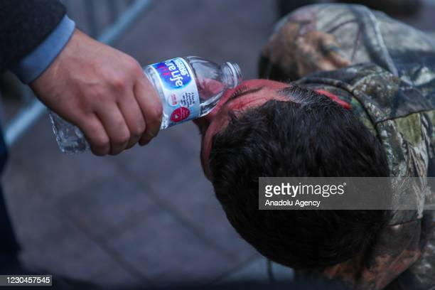Protester experiencing the effects of pepper spray douses his face with water on the grounds of the Capitol Building in Washington D.C., United...