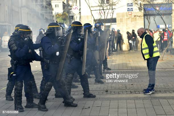 TOPSHOT A protester faces French riot police officers during a nationwide protest day against the government's economic and social reforms on...