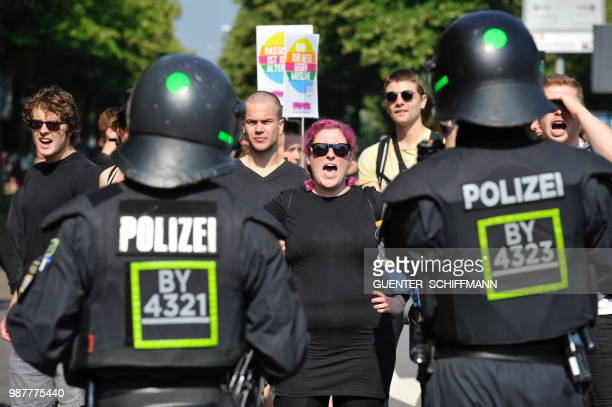 A protester faces policemen at the start of a twoday party congress of Germany's farright and antiimmigration party AfD in Augsburg southern Germany...