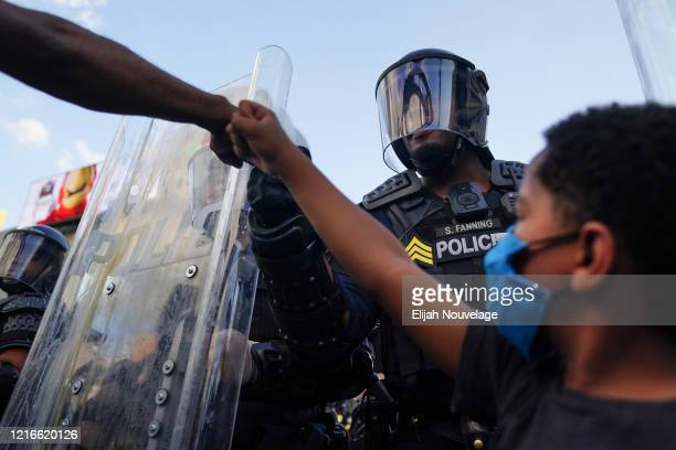 A protester fist bumps a police officer as a young boy raises his fist during a demonstration on May 31 2020 in Atlanta Georgia Across the country...