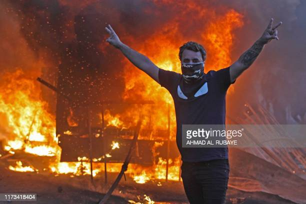 TOPSHOT A protester flashes the V for victory sign as a riot police vehicle burns behind him during clashes amidst demonstrations against state...
