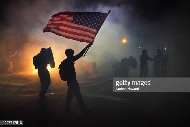 A protester flies an American flag while walking through tear gas fired by federal officers during a protest in front of the Mark O Hatfield US...