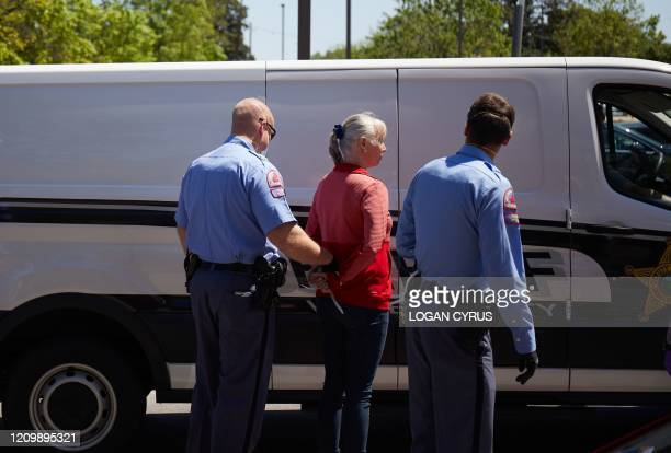 A protester from a grassroots organization called REOPEN NC is arrested after refusing to leave a parking lot during a demonstration against the...