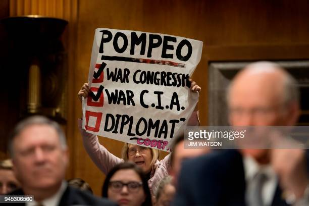 A protester from CodePink holds up a placard and shouts as US Senator Pat Roberts RKansas introduces Secretary of State nominee Mike Pompeo to...