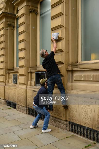 Protester from Extinction Rebellion attaches a notice to a branch of RBS bank detailing their alleged historic involvement in the slave trade during...