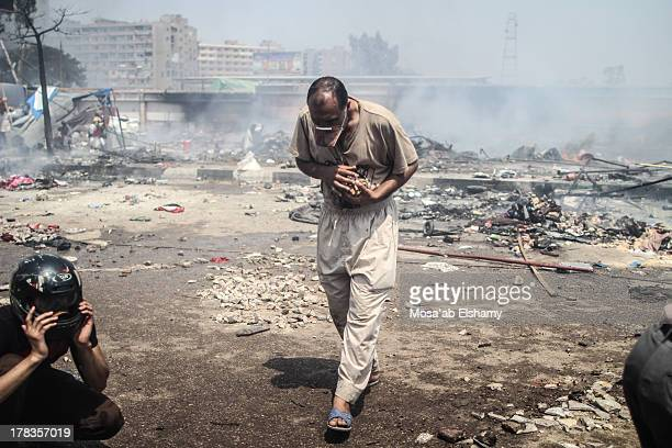 Protester gathers small rocks to throw at ecurity forces during the clearing of one of the two sit-ins of ousted president Morsi supporters, near...