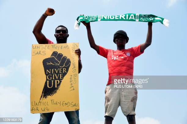 TOPSHOT A protester gesture while holding placard as another holds up a scarf with the colours of the Nigerian national flag during a demonstration...