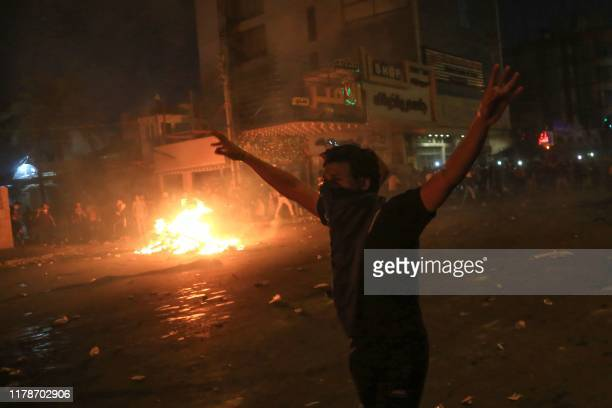Protester gestures as burning tyres light up the night skies during anti-government protests in the Shiite shrine city of Karbala, south of Iraq's...